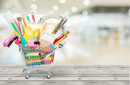 Colorful school supplies in shopping cart