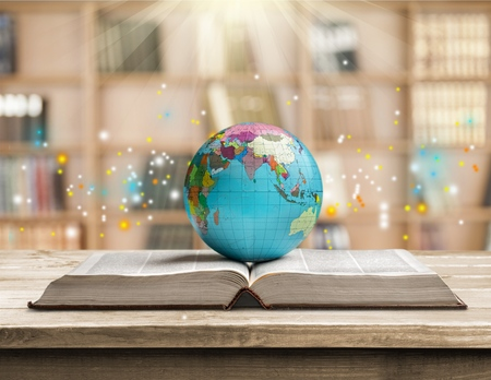 Ancient book and Earth globe with stars and universe art. Magic and space theme. Blue light on background. Planet concept. Place for text and infographic. Abstract history and astronomy theme.