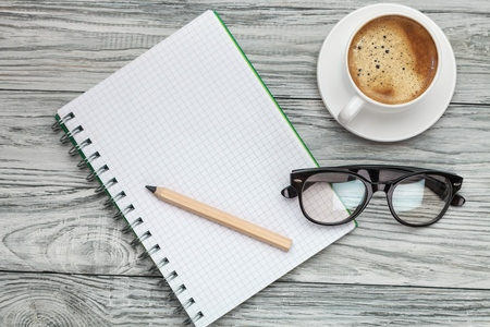 Concept SAFETY DATA SHEETS (SDS) message on notebook with glasses, pencil and coffee cup on wooden table. Safety & Health.