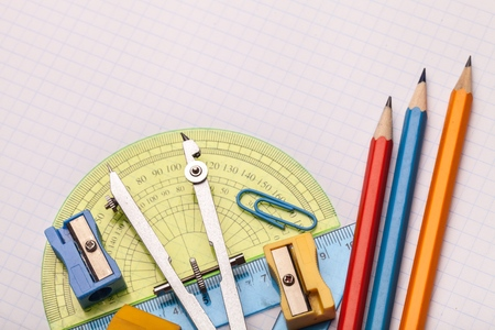 Mathematical instruments over the corner of a math graph paper with copy space for text. Math graphic tools concept. Stock Photo