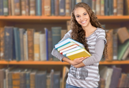 Woman reading a book in library. Portrait of college girl reading book in library