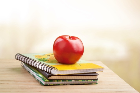 A stack of color books, eyeglasses, stationery on a table and text Back to school on green background Stock Photo