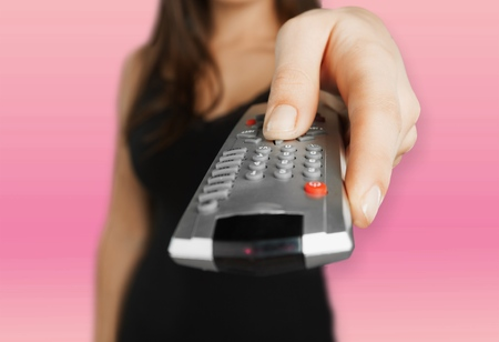 Woman holds remote control Stock Photo