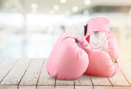 Pink boxing gloves on wooden background