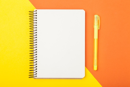 Top view flat lay picture with blank notepad page and different accessories on colored surface