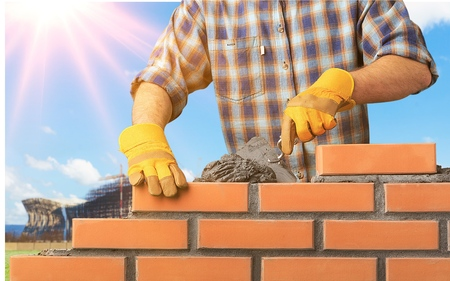 Close up of industrial bricklayer installing bricks on construction site 免版税图像