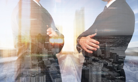 Two businessmen shaking hands together while standing by windows high up in an office tower overlooking the city