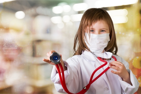 Little girl plays doctor examining baby doll patient with toy stethoscope Stock Photo
