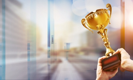Win concept,Man holding up a gold trophy cup is winner in a competition with cityscape background. Stock Photo