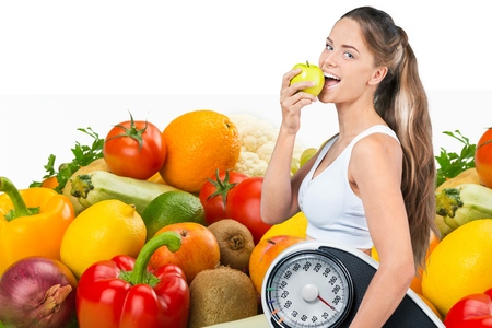 Fit woman holding a scale and apple