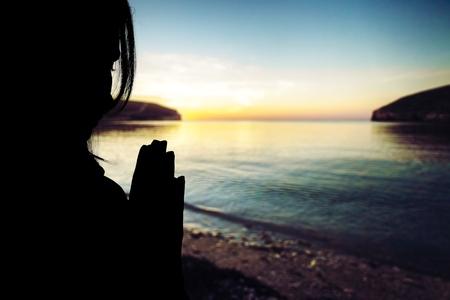 Silhouette woman prays at sunset