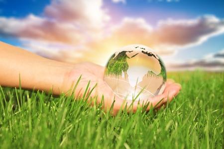 Hands holding earth on green grasses. Stock fotó
