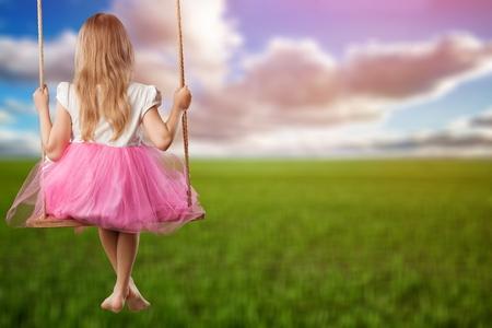 Happy Little Girl Smiling on Swing Stock fotó