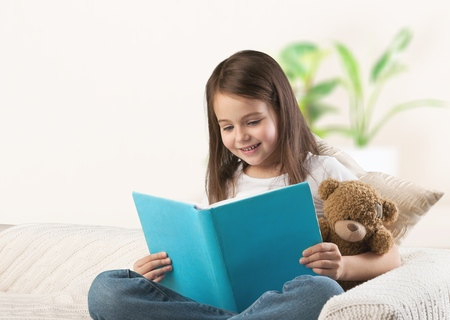 Child girl reading a book in bed before going to sleep
