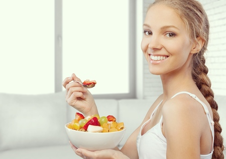 Young woman eating a healthy fruit salad