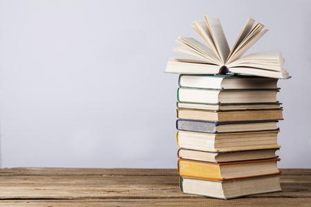 Otwórz książkę, książeczki w twardej oprawie i szkło powiększające na jasnym kolorowym tle. Powrót do szkoły. Skopiuj miejsce na tekst Zdjęcie Seryjne