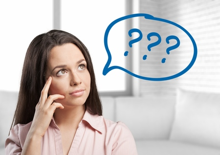 Portrait confused thinking young woman bewildered scratching head seeks a solution looking up at many question marks isolated on gray wall background. Human face expression Stock Photo