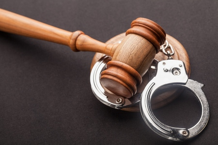 Gavel and handcuffs isolated on black Stockfoto - 96185851