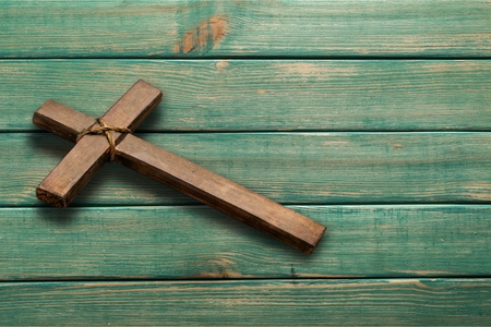 Rugged wood cross with rope hanging on antique rustic mint green wooden background; Christmas holiday background with painted copy space Stock Photo