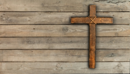 Rugged wood cross with rope hanging on antique rustic mint green wooden background; Christmas holiday background with painted copy space 版權商用圖片