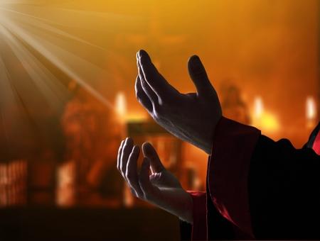 Silhouette rosary against cross in hand. Background sunrise Stockfoto