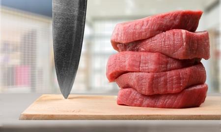 Butcher cutting pork meat on kitchen Stock Photo