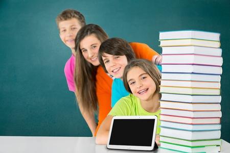 Students peeking behind pile of books on white background