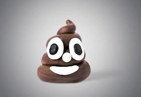 Poop emoticon on bright background. Minimal concept. Stock Photo