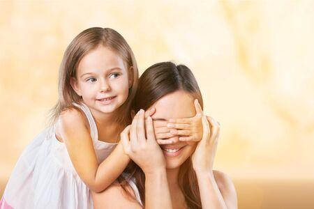 Young daughter closes hands eyes mom - isolated. Happy family people concept.