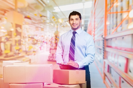 Manager In Warehouse Checking Boxes Using Digital Tablet Stock Photo