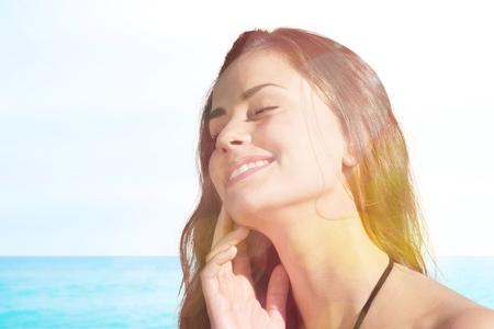 Smiling young woman applying sun block creme on beach