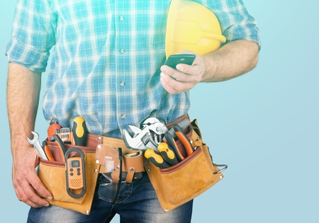 Close-up of construction worker sending text on mobile phone Archivio Fotografico