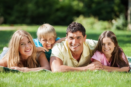 Nuclear Family Relaxing In a Park Together Stockfoto