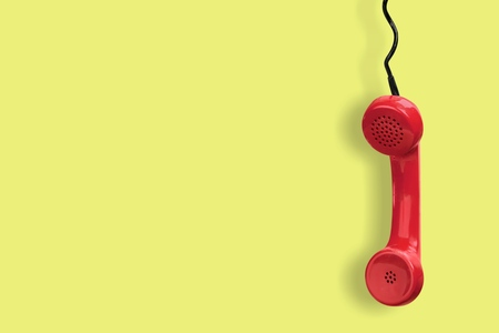 Red telephone receiver on yellow background Stock Photo - 96906673