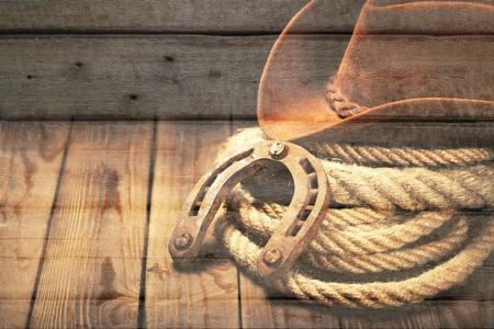 ラリアットラッソのアメリカンウエストロデオ古い馬蹄と、牧場の納屋でアンティークの木製イノシシに帽子と熟成レザーローパーブーツを持つ西
