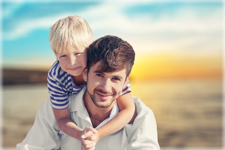Father holding son on shoulder. Portrait of happy father and son smiling and looking at camera. Father giving his son piggyback at beach. Stock Photo