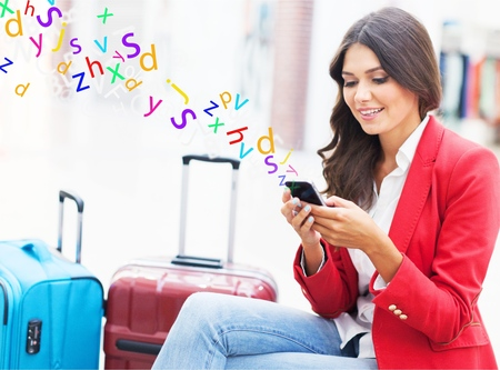 Airport business woman on smart phone at gate waiting in terminal. Air travel concept with young casual businesswoman sitting with hand luggage suitcase. Beautiful young mixed race female professional Stock Photo