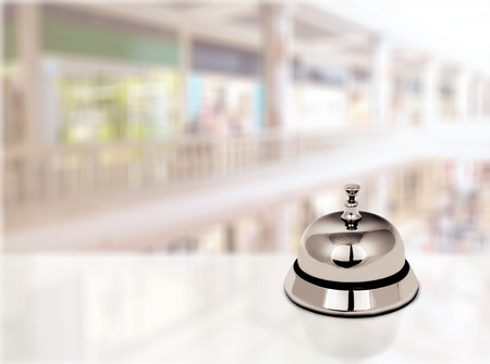 Hotel service bell on a table white glass and simulation hotel background. Concept hotel, travel, room