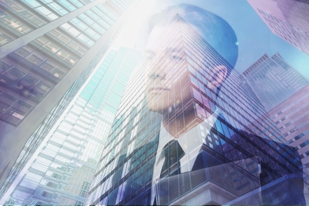 Double exposure of skyscraper and businessman with digital tablet