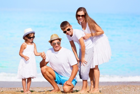 Happy beautiful family on a beach during summer vacation