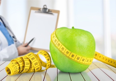 Concept of healthy and proper food with tapemeasure
