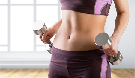 Close-up of torso of female holding barbells Stock Photo