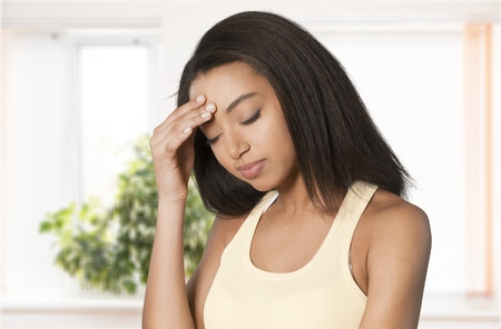 Young sad woman sits alone front of the window. Crying girl. Allergy, illness, depression, stress concept. Stock Photo