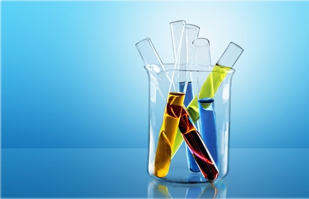 Different laboratory glassware with color liquid and with reflection.