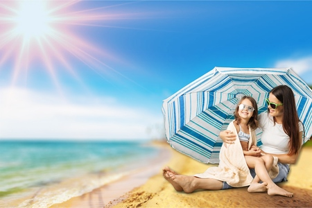 Mother And Daughter Under Beach Umbrella Putting On Sun Cream Stock Photo