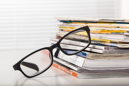 Stack of magazines with glasses Stock Photo