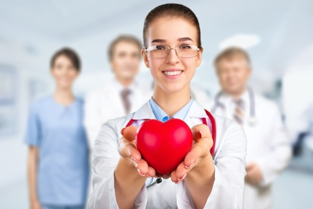 Female doctor hold in arms red heart Banque d'images