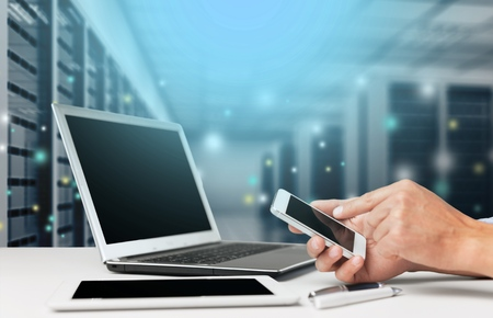 Human hand working with smartphone and computer