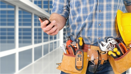 Close-up of construction worker sending text on mobile phone Foto de archivo
