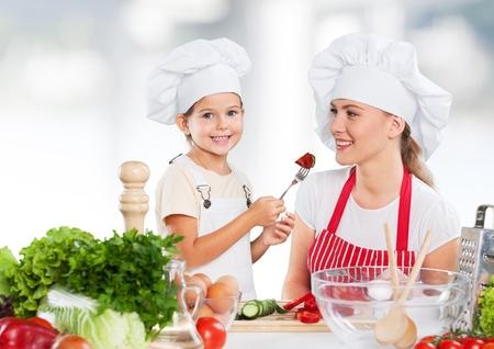 kid daughter feeding mother vegetables in kitchen
